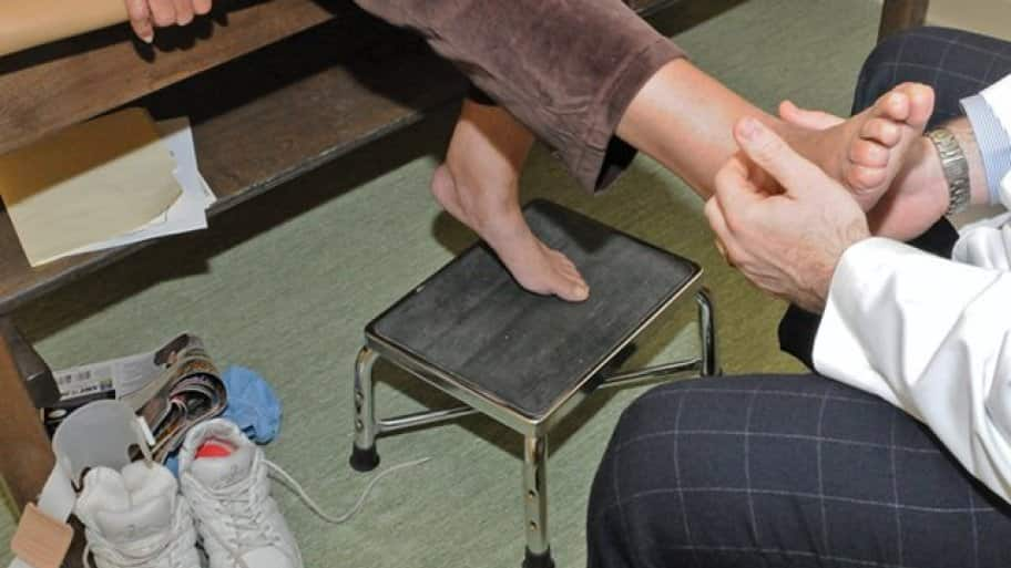 doctor checks nerve sensitivity on a patient's foot.