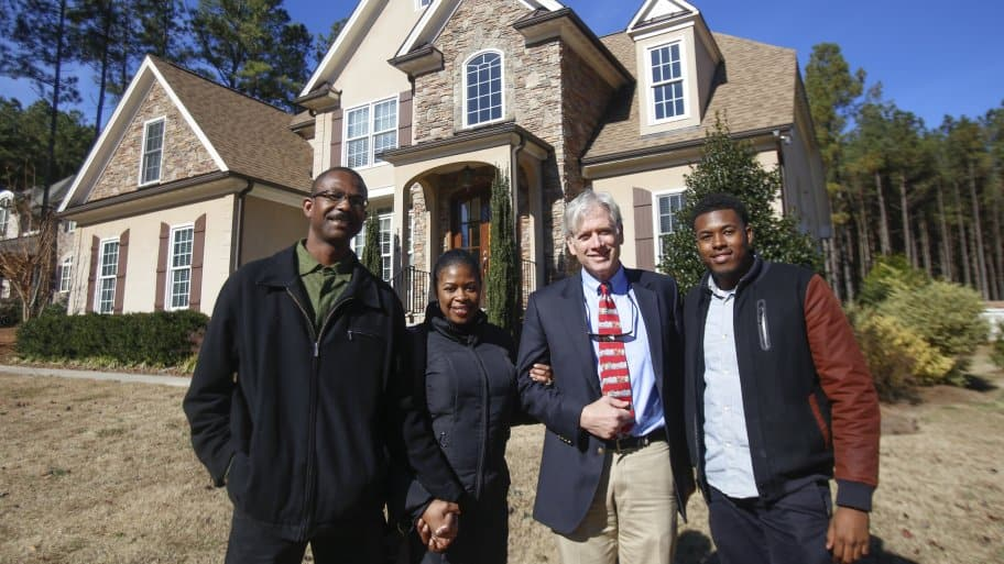 A family stands in front of a home after a sale.