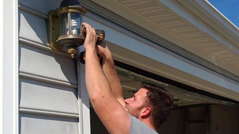 handyman using drill to screw light fixture onto garage