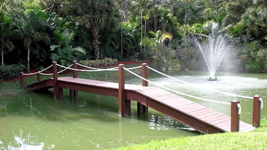 bridge over backyard pond and waterfall